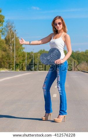 Beautiful girl hitchhiking on the road traveling - stock photo