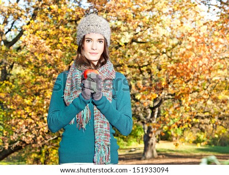 Beautiful girl hold an apple on sunny autumn-day in park