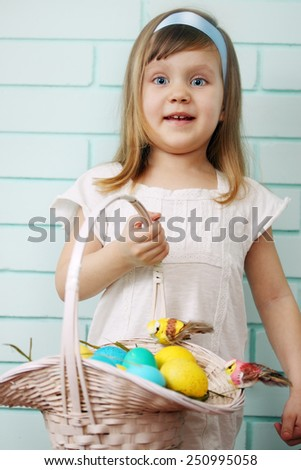 Beautiful girl holding a basket with colored eggs