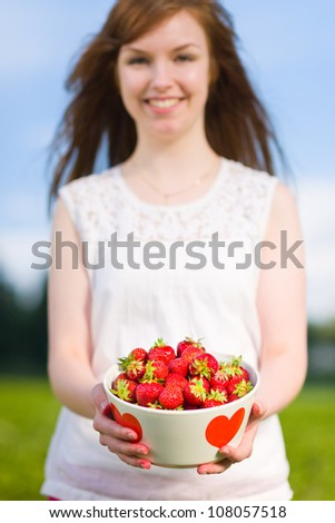 Beautiful girl holding a bowl of fresh strawberries, focus on the bowl - stock photo