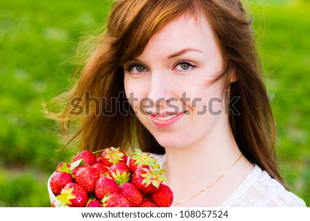 Beautiful girl holding a bowl of fresh strawberries, focus on the eyes - stock photo