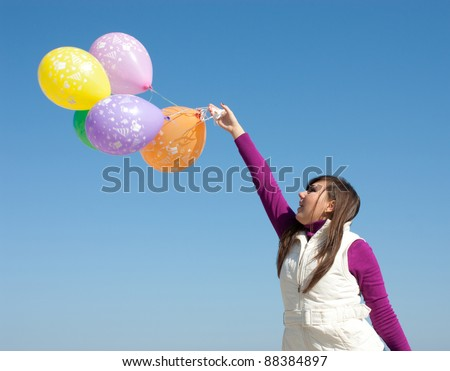 Beautiful girl holding a bunch of colorful balloons