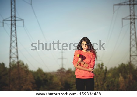 Beautiful girl holding a flower against the masts of power lines - stock photo