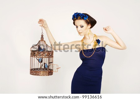 Beautiful girl holding a gold cage with blue butterflies