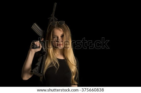 Beautiful girl holding a gun in black background