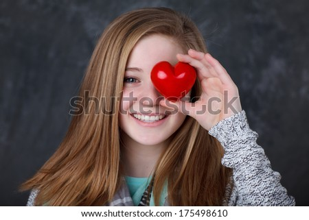 beautiful girl holding a heart in front of her eye - stock photo