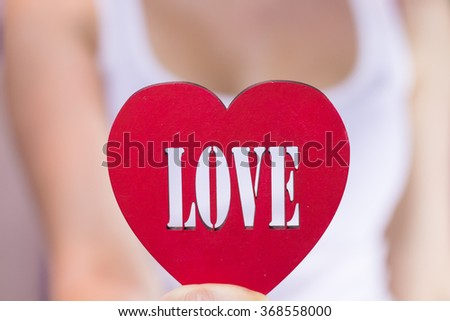 Beautiful girl holding a heart in hands - stock photo