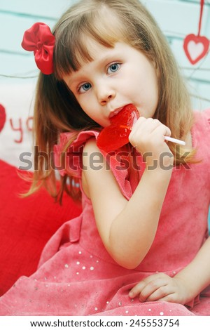 Beautiful girl holding a lollipop in the shape of heart