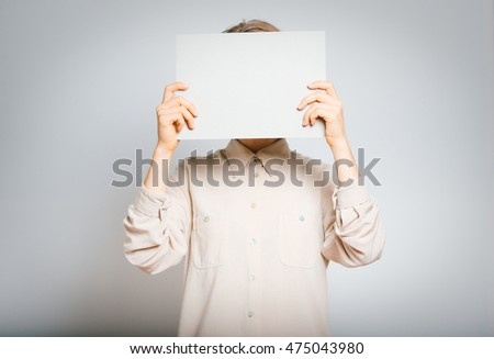 beautiful girl holding a sheet of paper for your text, close-up, isolated on a gray background