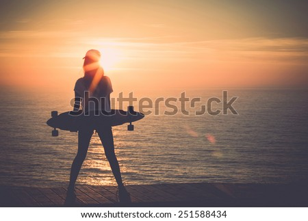 Beautiful girl holding a skateboard with the sunset in the background - stock photo