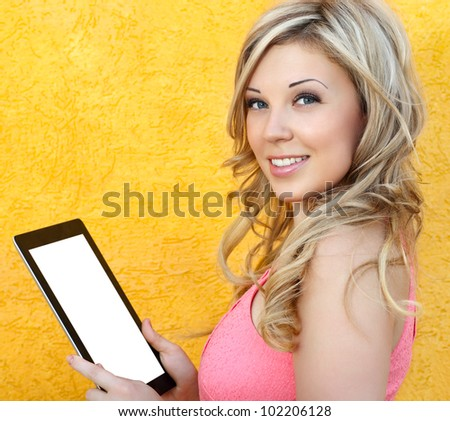 beautiful girl holding a tablet touch pad computer gadget on a yellow background - stock photo