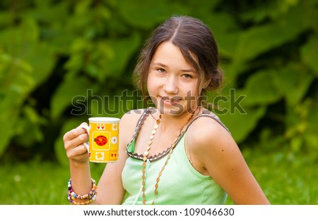 Beautiful girl holding cup in the park, close-up - stock photo