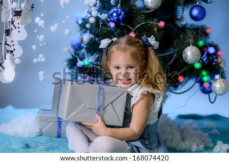 beautiful girl holding gift near a Christmas fir-tree - stock photo
