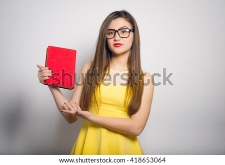 beautiful girl holding or reading a book in a yellow dress, closeup isolated on white background - stock photo