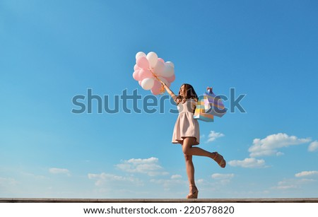 Beautiful girl holding shopping bags and colored balloons over blue sky. - stock photo