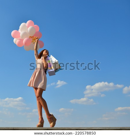 Beautiful girl holding shopping bags and colored balloons over blue sky - stock photo