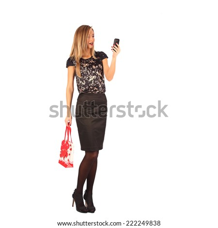 Beautiful girl holding shopping bags and taking selfie with cell phone isolated on white background - stock photo