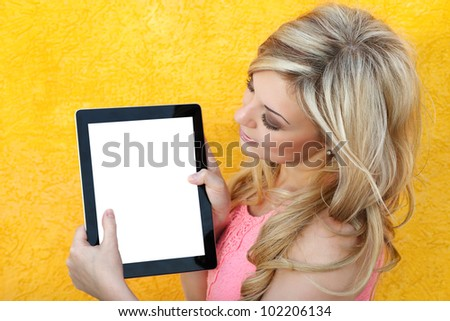 beautiful girl holding the tablet touch pad computer gadget and looking at the screen on a yellow background - stock photo
