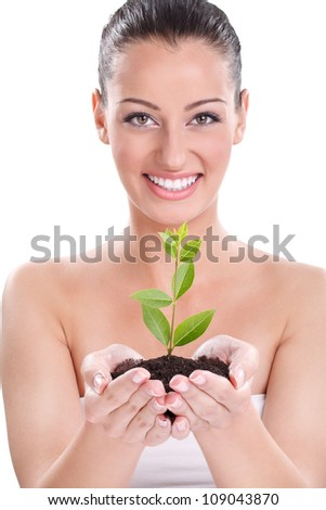Beautiful girl holding young plant growing from the ground - stock photo