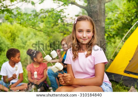 Beautiful girl holds sticks with marshmallows - stock photo