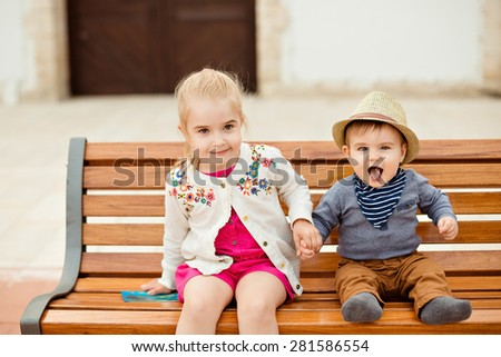 Beautiful girl holds the hand of brother laughing baby boy in a hat, sitting on brown bench in summer - stock photo