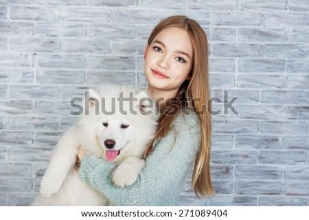 Beautiful girl huging Samoyed dog - stock photo