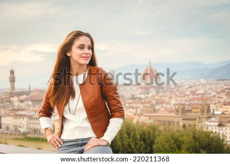 Beautiful girl impressed view the panorama of Florence in autumnal colors. - stock photo