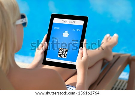 beautiful girl in a bathing suit lying on a deck chair by the pool and holding a tablet computer with mobile wallet and liner ticket on a screen - stock photo