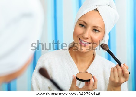 Beautiful girl in a bathrobe applying blush to her face in the bathroom - stock photo