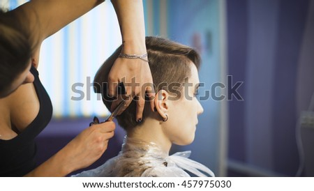 Beautiful girl in a beauty salon. Professional stylist makes to the woman a new stylish haircut. Self-confident young business woman in the client chair