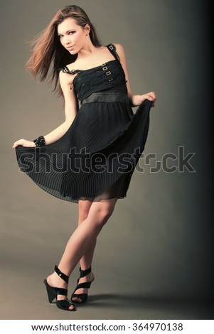 Beautiful girl in a black dress is dancing. Pretty woman with green eyes. - stock photo