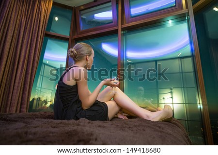 Beautiful girl in a black dress sitting on the bed with glass - stock photo