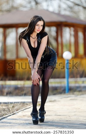 Beautiful girl in a black suit with long brown hair, shapely long legs and large breasts posing in nature. Brunette in a black suit in the nature. Blue-eyed brunette in black with big breasts. - stock photo