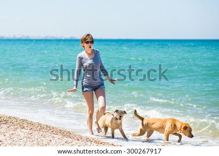 Beautiful girl in a blue blouse and shorts walking with dogs on the beach