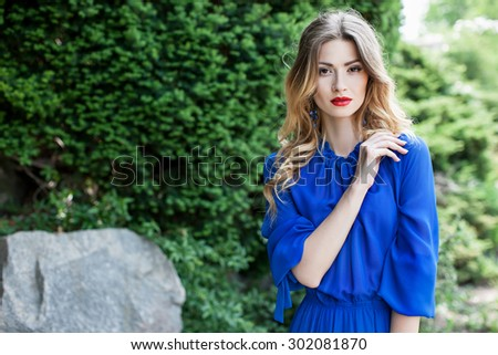 Beautiful girl in a blue dress in the park. An attractive woman in a blue dress on a background of green trees, her face beautiful make-up. Girl with red lipstick. Elegant lady in beautiful dress - stock photo