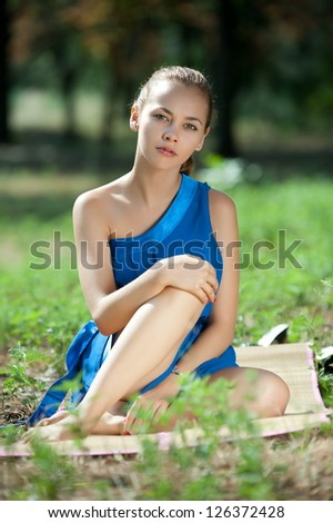 Beautiful girl in a blue dress lying on the grass in the park