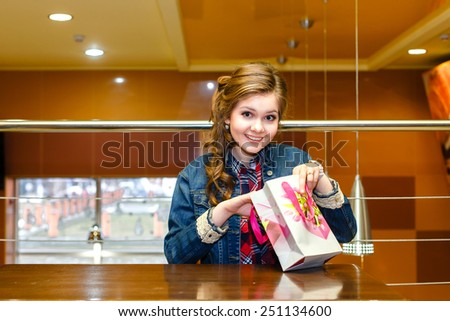 Beautiful girl in a cafe opens a gift bag and smiling - stock photo