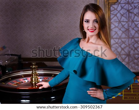 beautiful girl in a casino near the roulette. Girl playing in casino.