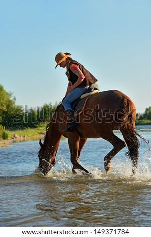 Beautiful girl in a cowboy suit on Horse riding