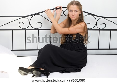 Beautiful girl in a dress and shoes on high heels sitting on a bed studio photography - stock photo