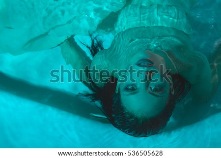 beautiful girl in a dress dives under the water