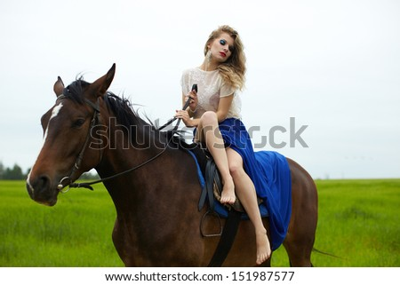 beautiful girl in a dress on a horse in a green field