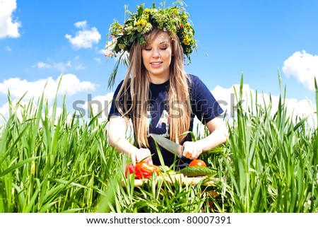 beautiful girl in a field of flowers cut vegetables - stock photo