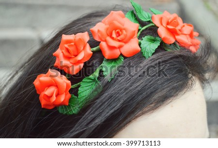 beautiful girl in a flower wreath made of polymer clay.hairpin in the shape of a flower on the hair of a young woman