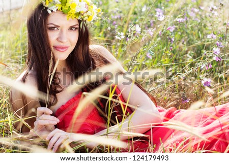 beautiful girl in a flowers wreath on the nature