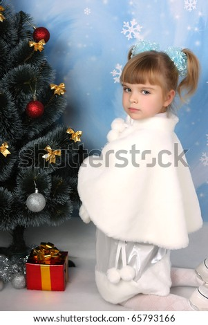 beautiful girl in a fur cloak around the Christmas Tree