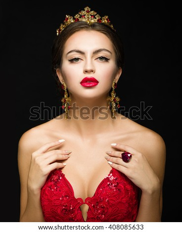 Beautiful girl in a golden crown and earrings on a dark background. Ring in the heart shape. Red dress and red lipstick.