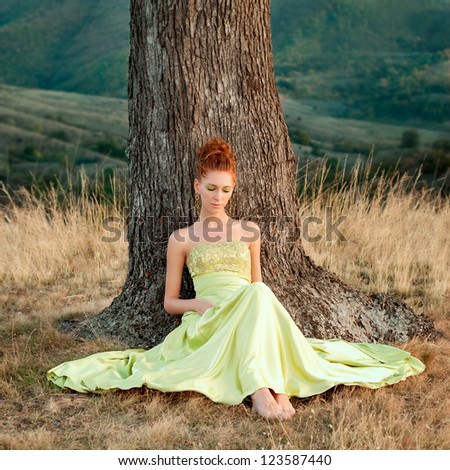 Beautiful girl in a green dress sitting under a tree - stock photo