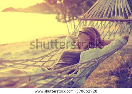 beautiful girl in a hammock on the beach, watching the sunset. Image with retro filter - stock photo
