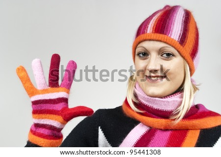 beautiful girl in a hat and gloves, shows his hand on the background - stock photo